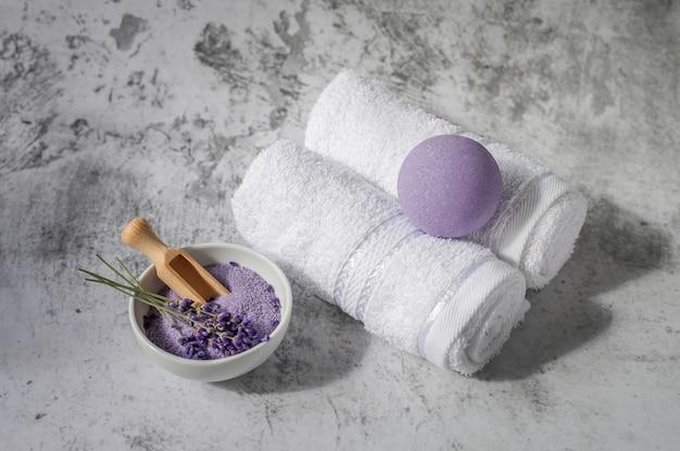 Gedrehte badetücher mit lavendel und badesalz auf hellgrau. badekurorttücher gegen eine strukturierte wand. minimalismus, weicher fokus. spa.