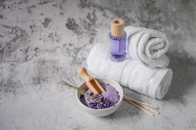 Gedrehte badetücher mit lufterfrischer und badesalz auf hellgrau.
