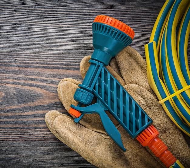 Gedrehte hand sprühen garten gummischlauch sicherheitshandschuhe auf holzbrett