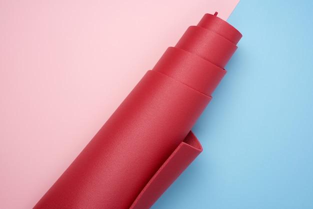 Gedrehte rote neoprenmatte für yoga und sport auf rosa blauem hintergrund
