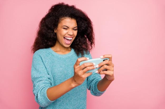 Gedrehtes foto der fröhlichen verrückten verrückten frau, die sich über das abschließen des levels im videospiel freut und isolierte rosa pastellfarbenwand schreit