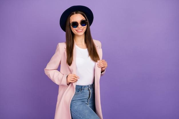Gedrehtes foto von attraktivem inhalt, hübsches mädchen, das ihren modernen mantel berührt, freizeit-wochenendurlaub genießen, stilvolle trendige kleidung einzeln auf violettem hintergrund tragen
