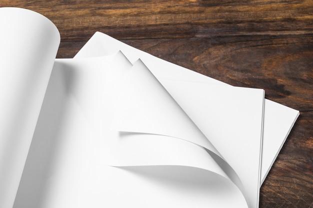 Gedrehtes weißes leeres papier über dem holztisch