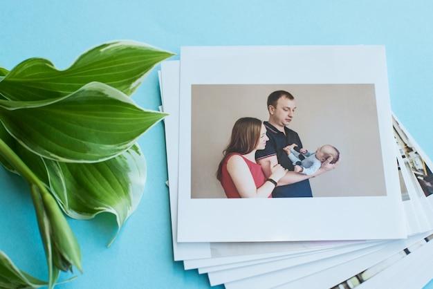 Gedruckte fotos, rahmenkarten, auf einem blauen hintergrund mit einer weißen blume. familienfoto