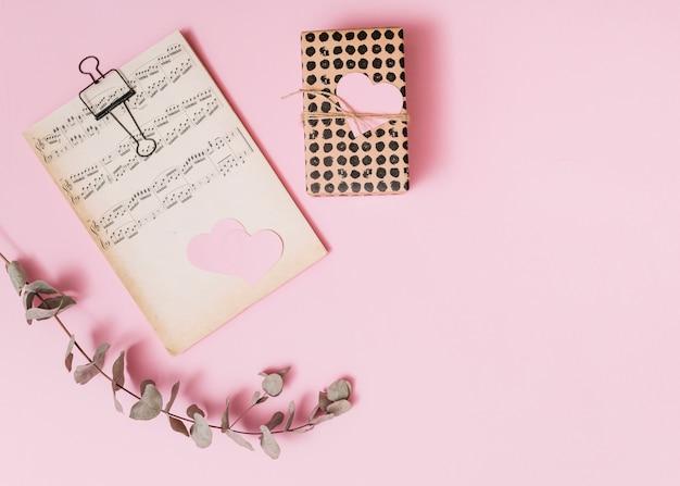 Gedruckte musik in der nähe von geschenkschachtel und zweig