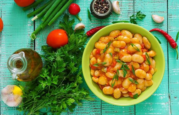 Gedünstete weiße bohnen mit gemüse in tomatensauce