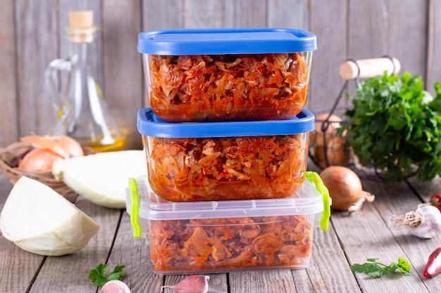 Gedünsteter kohl in einem behälter auf einem hölzernen hintergrund zum einfrieren. tiefkühlkost, gesundes essen