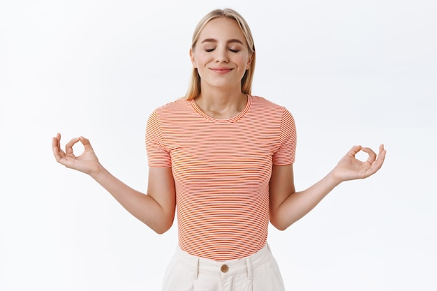 Geduld der schlüssel zum erfolg. attraktive ruhige, erleichterte blonde kaukasierin in gestreiftem t-shirt, enge augen und lächeln sammeln entspannung, breiten die hände seitlich aus, machen mudra-zeichen, meditieren, praktizieren yoga