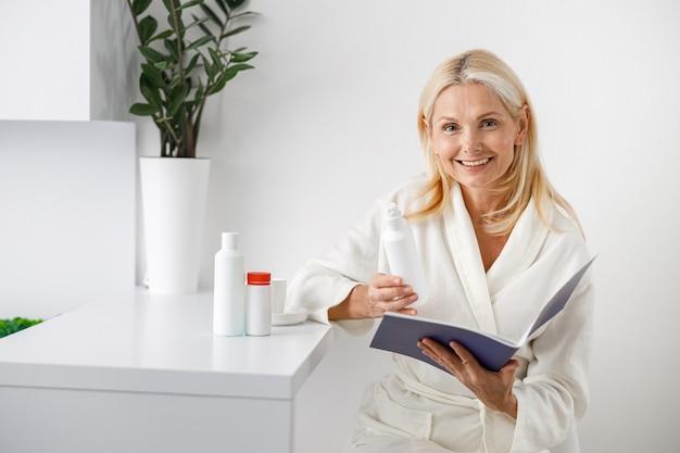 Geduldige ältere blonde frau, die nahe der rezeption steht und eine broschüre mit schönheitsbehandlungen hält.