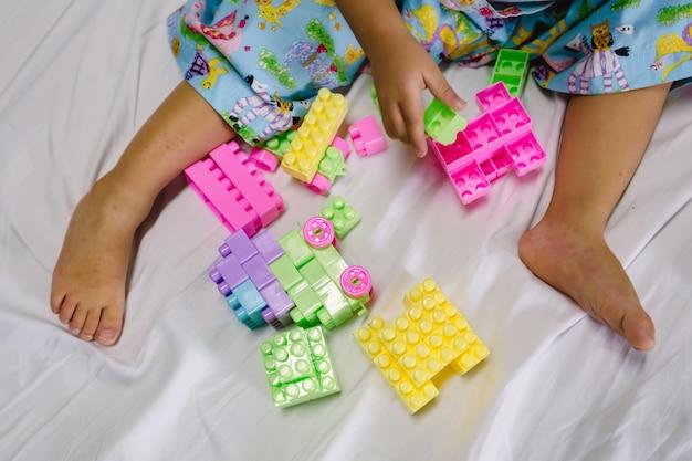Geduldige kinder, die backsteinbauspiel auf geduldigem bett spielen
