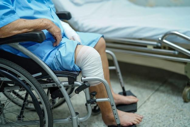 Geduldiger unfall der asiatischen älteren frau am knie mit verband auf rollstuhl im krankenhaus.