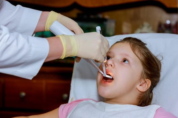 Geduldiges fröhliches kind mit dem lockigen roten haar. mädchen lächelnd im zahnarztstuhl.