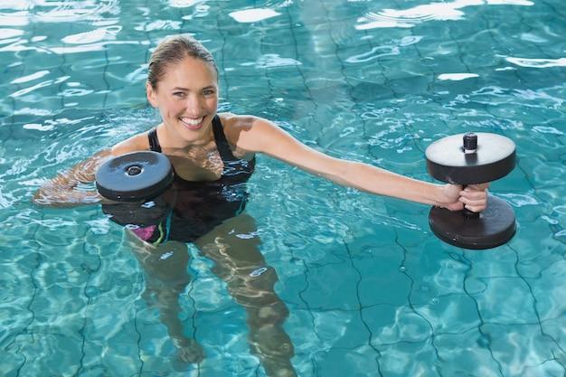Geeignete blondine, die mit schaumdummköpfen im swimmingpool in der freizeitmitte ausarbeitet