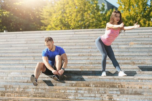 Geeignete eignungsfrau und -mann, die übungen am park draußen ausdehnend tut