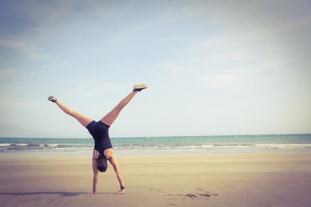 Geeignete frau cartwheeling auf dem sand