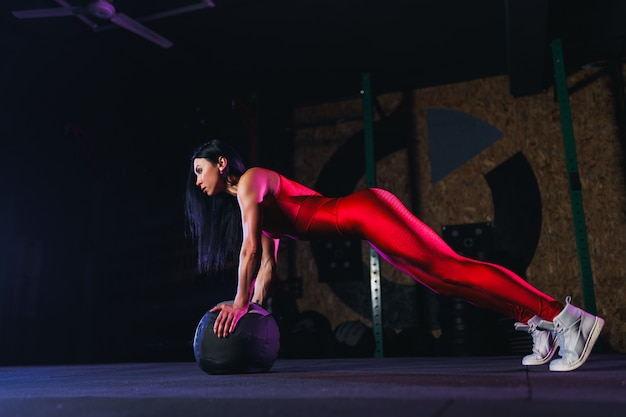 Geeignete frau der junge, die das handeln drückt, oder plankenübung auf medizinball an der turnhalle