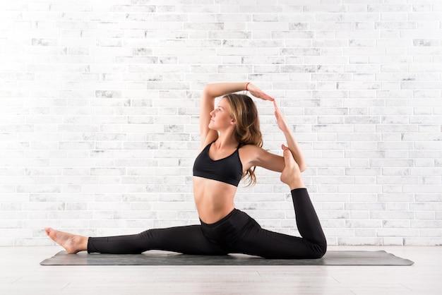 Geeignete frau der junge, die yogahaltung auf matte tut