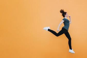 Geeignete Frau, die an der orange Wand springt