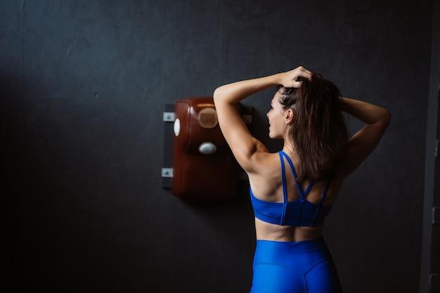 Geeignete frau, die auf der kamera aufwirft. personal trainer zeigt ihre form. schönheit des modernen sports.