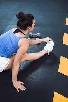 Geeignete frau, die ihr bein im fitnessclub ausdehnt