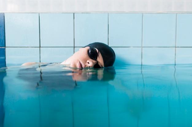 Geeignete frau, die im pool sich entspannt
