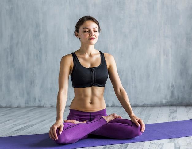 Geeignete frau, die in lotussitz beim meditieren steht