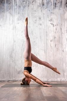 Geeignete frau, die veränderung der sirsasana yogahaltung tut