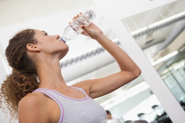Geeignete frau, die von der wasserflasche trinkt
