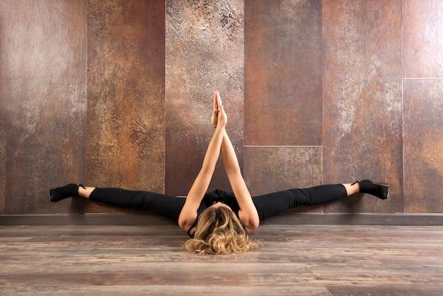 Geeignete frau, die yoga auf bretterboden ausübt