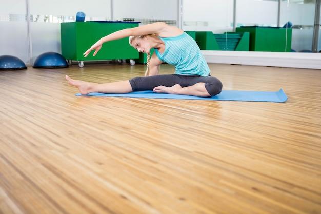 Geeignete frau, die yoga auf matte im eignungsstudio tut