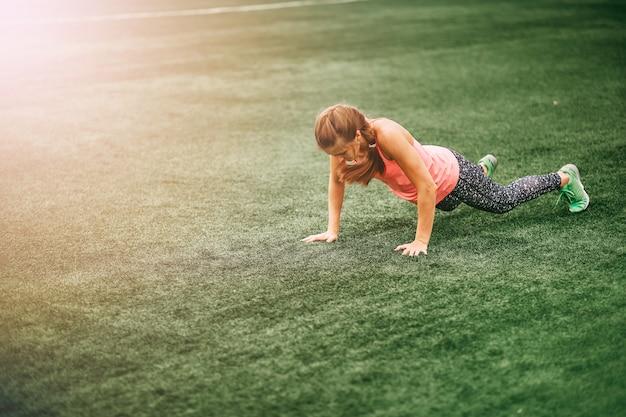 Geeignete frau in heller sportkleidung, zum von burpees auf dem grünen gras zu tun
