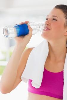 Geeignete frau mit trinkwasser des tuches in der turnhalle