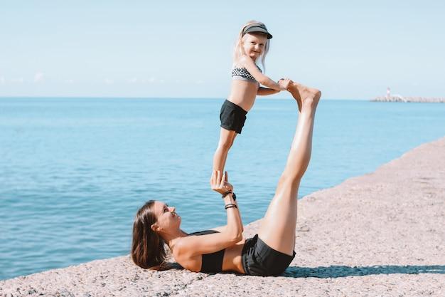 Geeignete frauenmutter der junge mit dem kleinen netten mädchen, das zusammen auf dem morgenstrand, gesunder lebensstil, sportfamilie trainiert