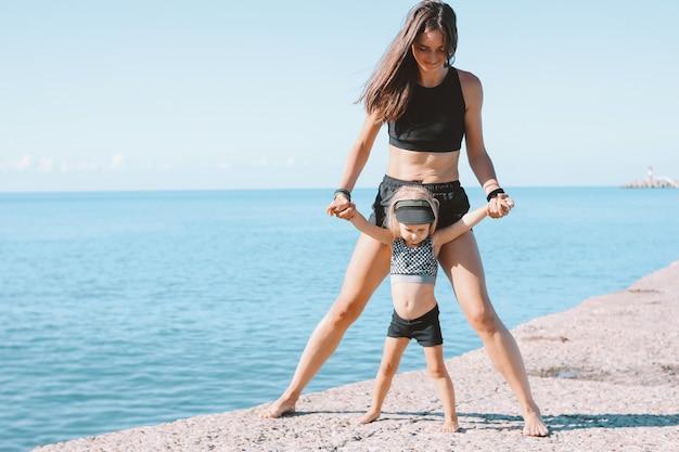 Geeignete frauenmutter der junge mit dem kleinen netten mädchen, das zusammen auf morgenstrand trainiert