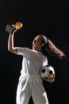 Geeignete fußballfrau, die trophäe hält