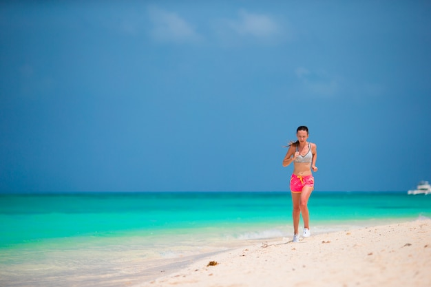 Geeignete junge frau des sports, die entlang tropischen strand in ihrer sportkleidung läuft
