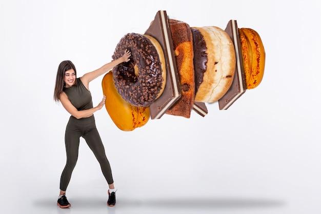 Geeignete junge frau, die bonbons, süßigkeiten und kohlenhydrate ablehnt