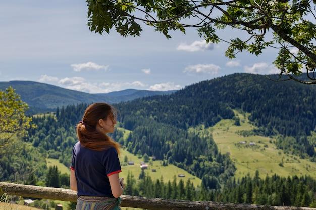 Geeignete junge frau, die in den bergen stehen auf einer felsigen gipfelkante mit dem rucksack und pfosten heraus schauen über einer alpinen landschaft wandert