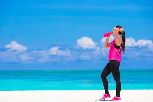 Geeignete junge frau, die übungen auf tropischem weißem strand in ihrer sportkleidung tut