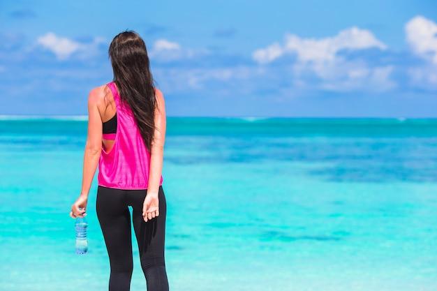 Geeignete junge frau mit flasche wasser auf tropischem weißem strand