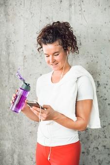 Geeignete junge frau mit wasserflasche unter verwendung des mobiltelefons
