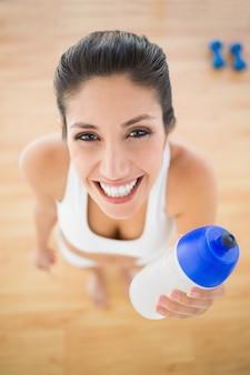 Geeignete lächelnde frau, die sportflasche hält