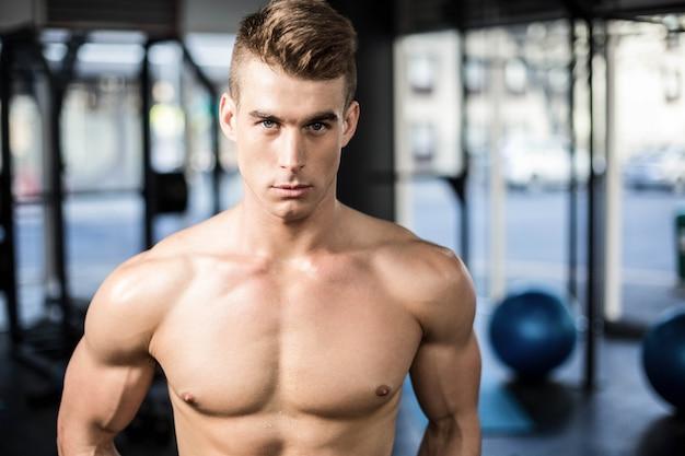 Geeignete muskulöse mannaufstellung hemdlos an der turnhalle