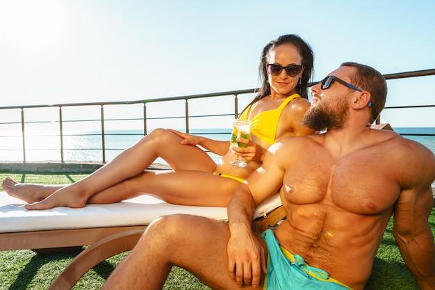 Geeignete muskulöse paare in der badebekleidung, die nahe dem pool sich entspannt