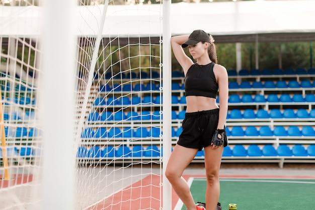 Geeignete sportliche frau auf dem fußballplatz bereit, sportaktivitäten zu trainieren und auszuüben
