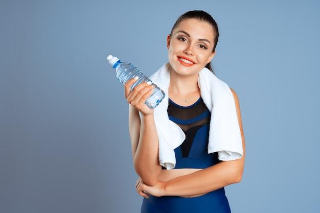 Geeignete sportliche frau, die mineralwasserflasche in ihrer hand hält