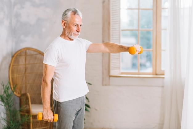 Geeigneter älterer mann, der zu hause mit orange hanteln trainiert