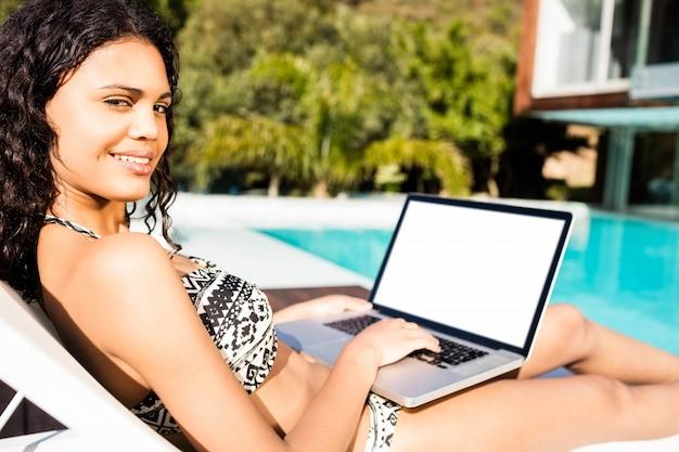 Geeigneter brunette, der auf liegestuhl liegt und laptop am pool verwendet