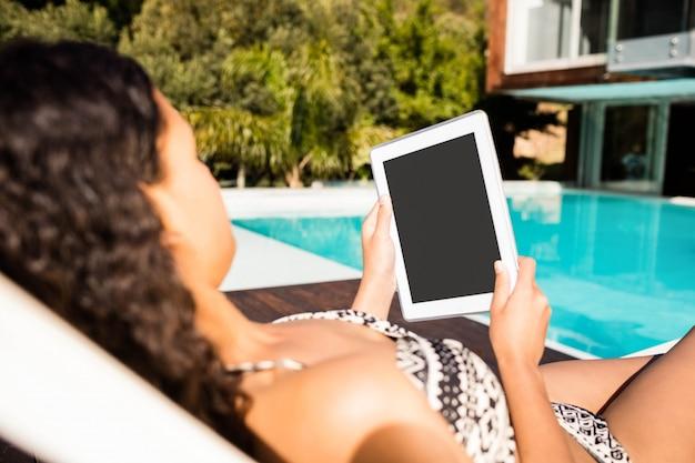 Geeigneter brunette, der auf liegestuhl liegt und tablette am pool verwendet