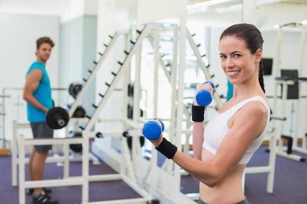 Geeigneter brunette, der mit blauen dummköpfen trainiert